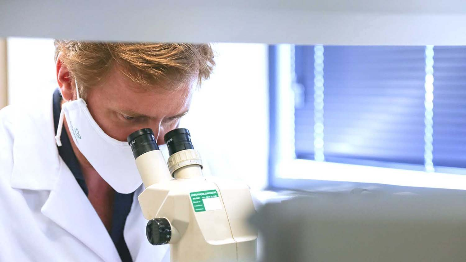 Laboratory men looking in a microscope